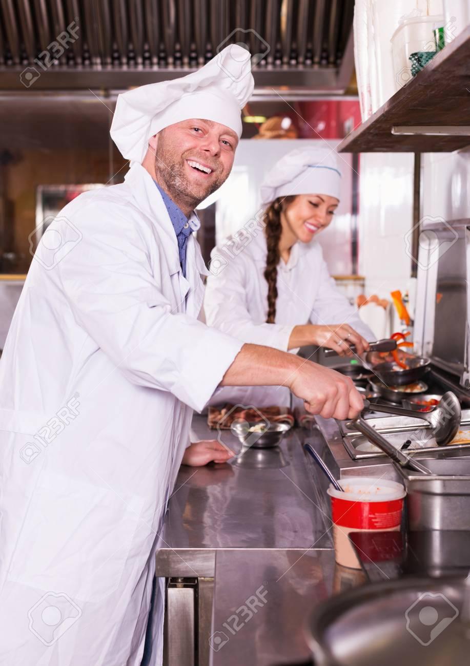 La Cuisine De Bistrot cuisiniers gai et heureux accueillir les clients à la cuisine de bistrot et  souriant