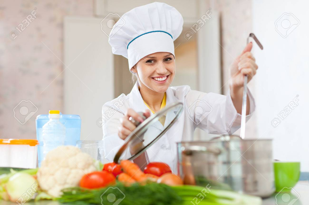 professional cook in white hat works in the kitchen stock photo