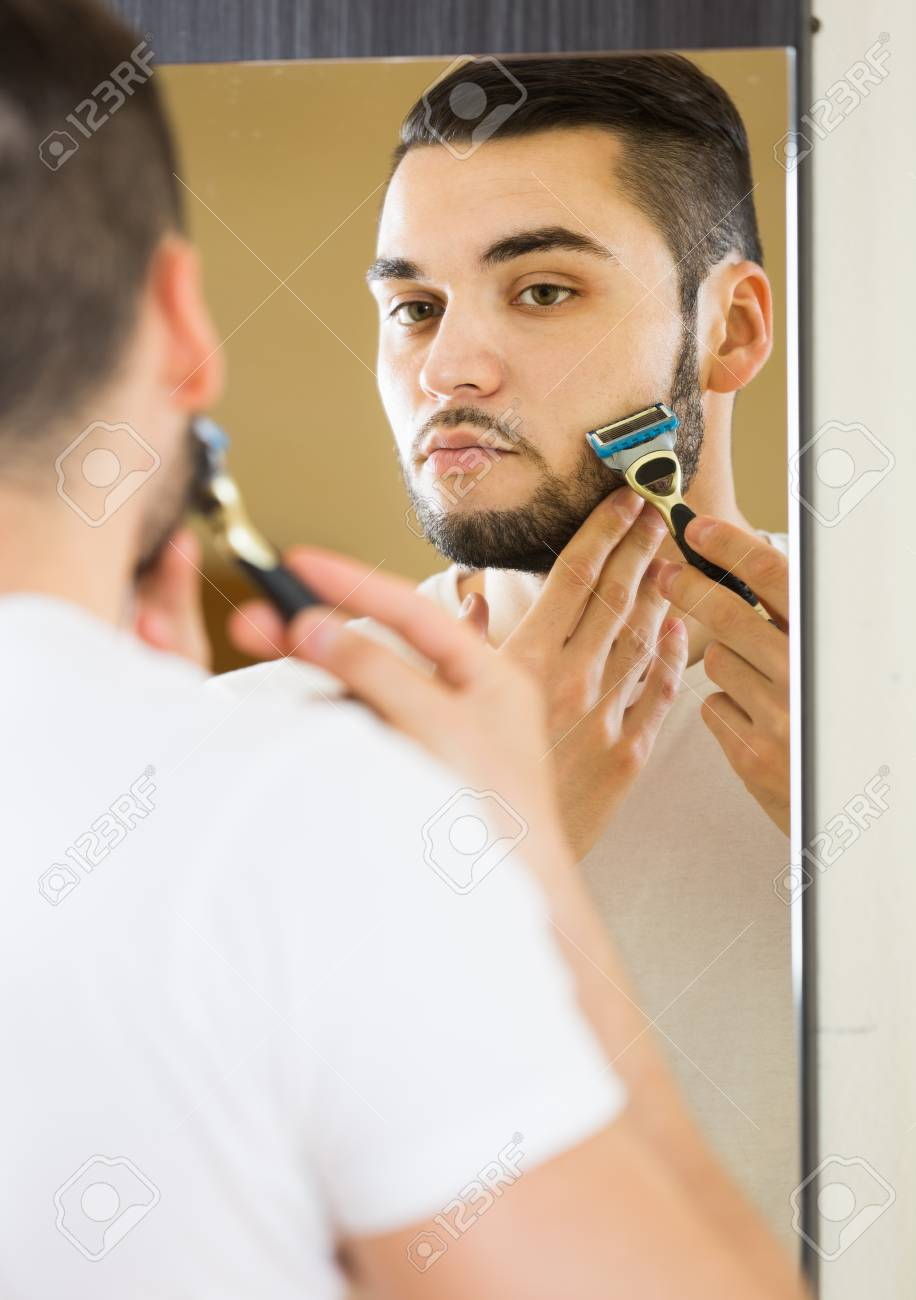 european man looking at mirror and shaving face with razor stock