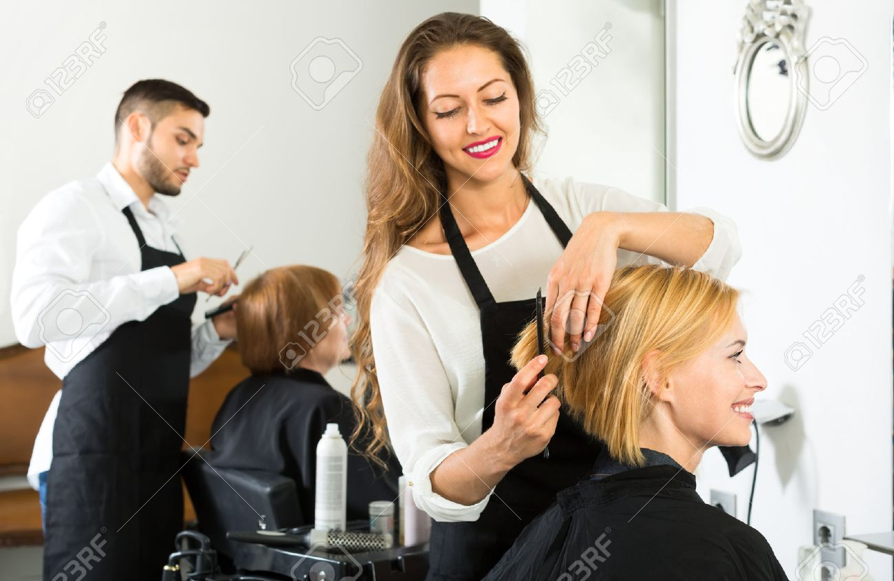 Smiling client sitting in a hair salon while hairdresser is combing her hair. Focus on client Stock Photo - 42931301
