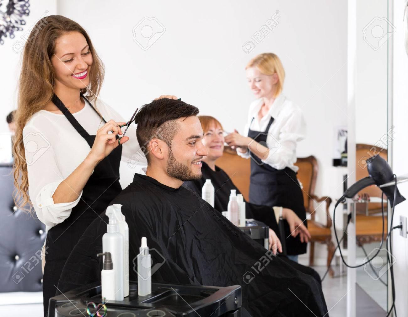 Cheerful young guy cuts hair at the hair salon Stock Photo - 42931302