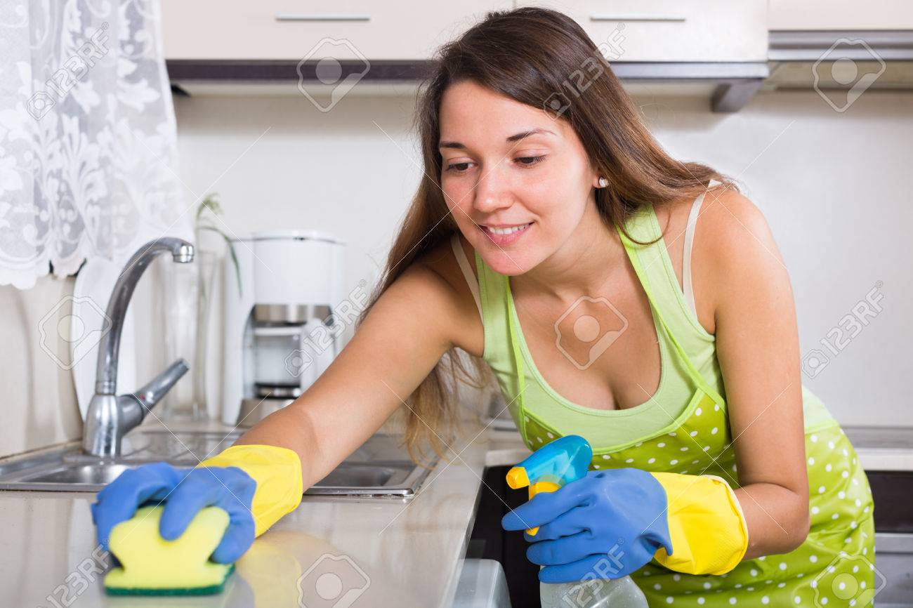 young woman in apron cleaning kitchen sink at home stock photo