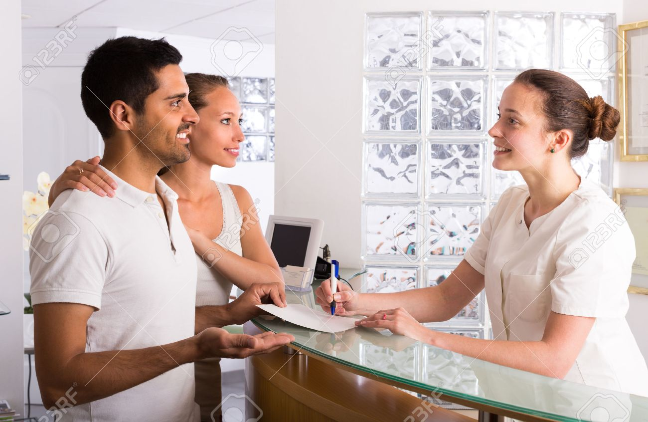 Positive young couple talking with secretary at reception in the clinic Stock Photo - 43507709