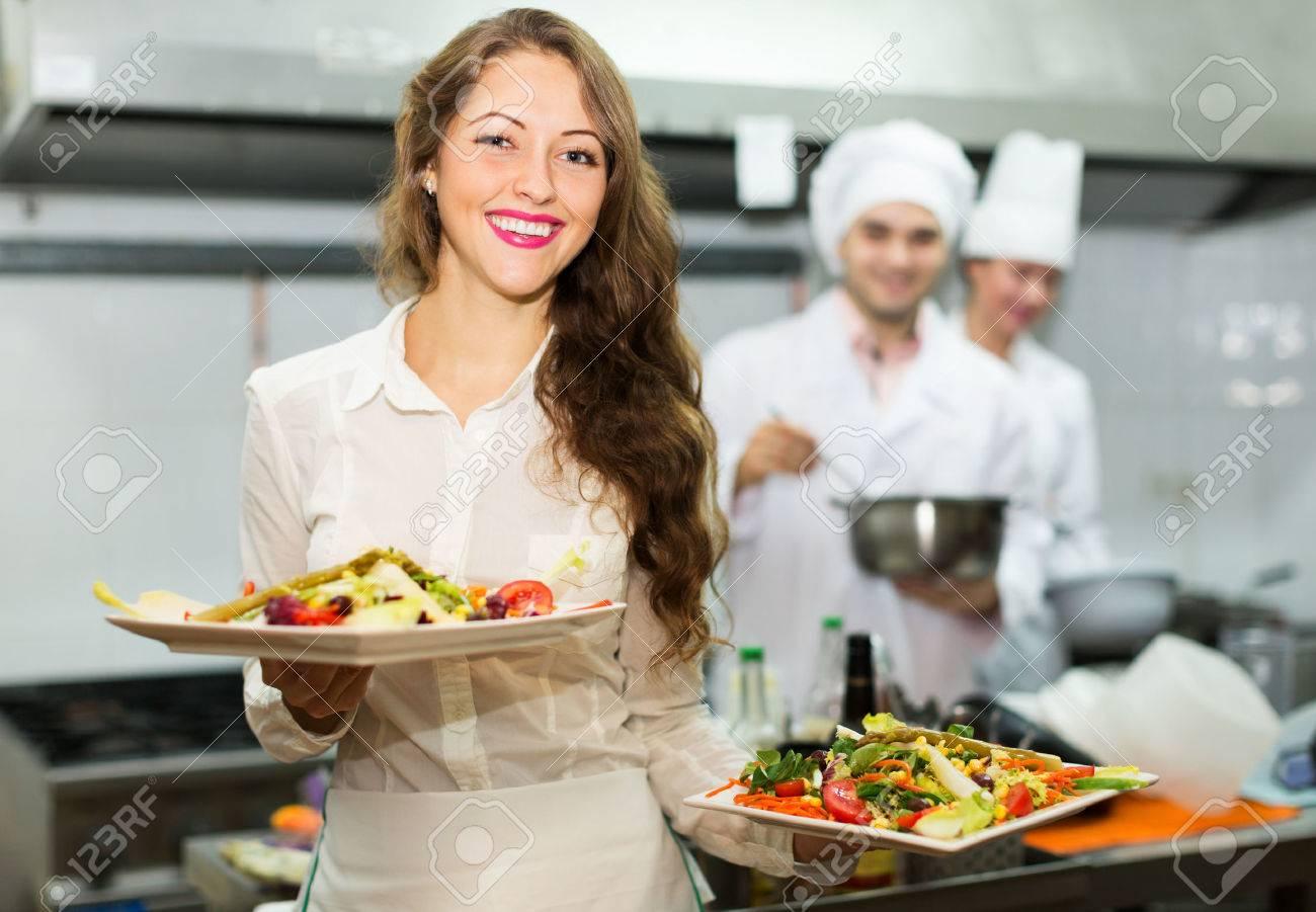Restaurant Kitchen Chefs team of chefs and young beautiful waiter at restaurant kitchen