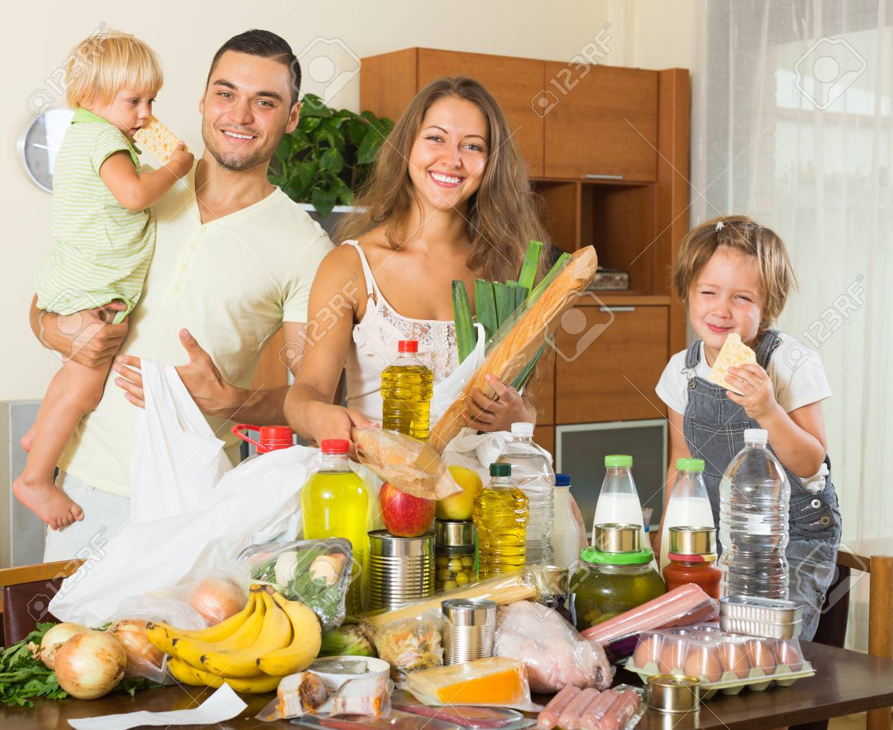 Cheerful Family Of Four With Bags Of Organic Food At Home Stock Photo    43729701
