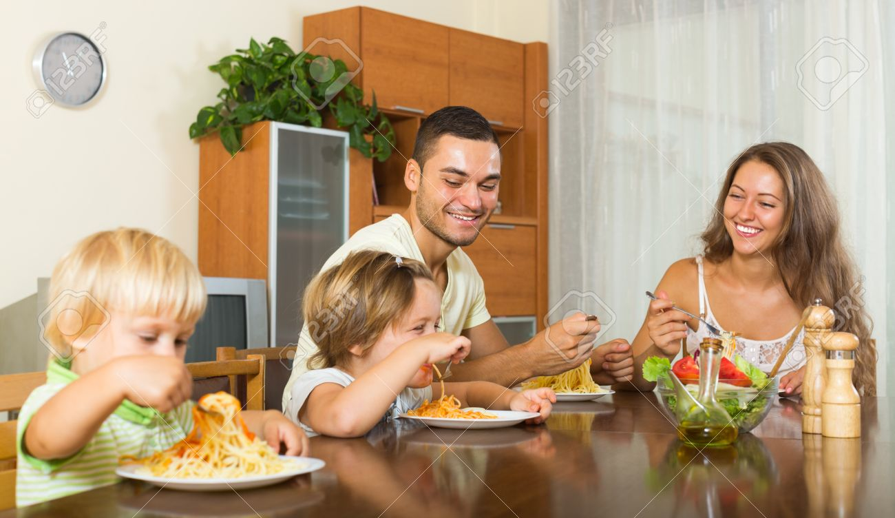 happy family of four people having lunch with pasta at home together - 43730154