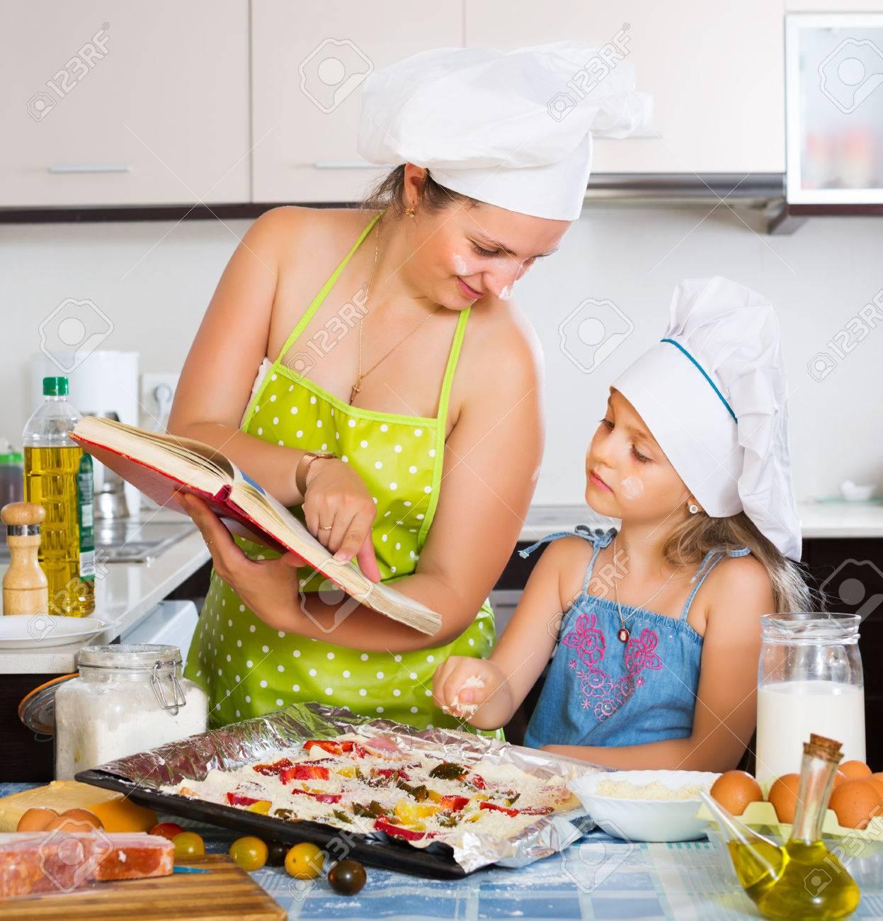 maman en tablier et sa petite fille décorer pizza à la cuisine