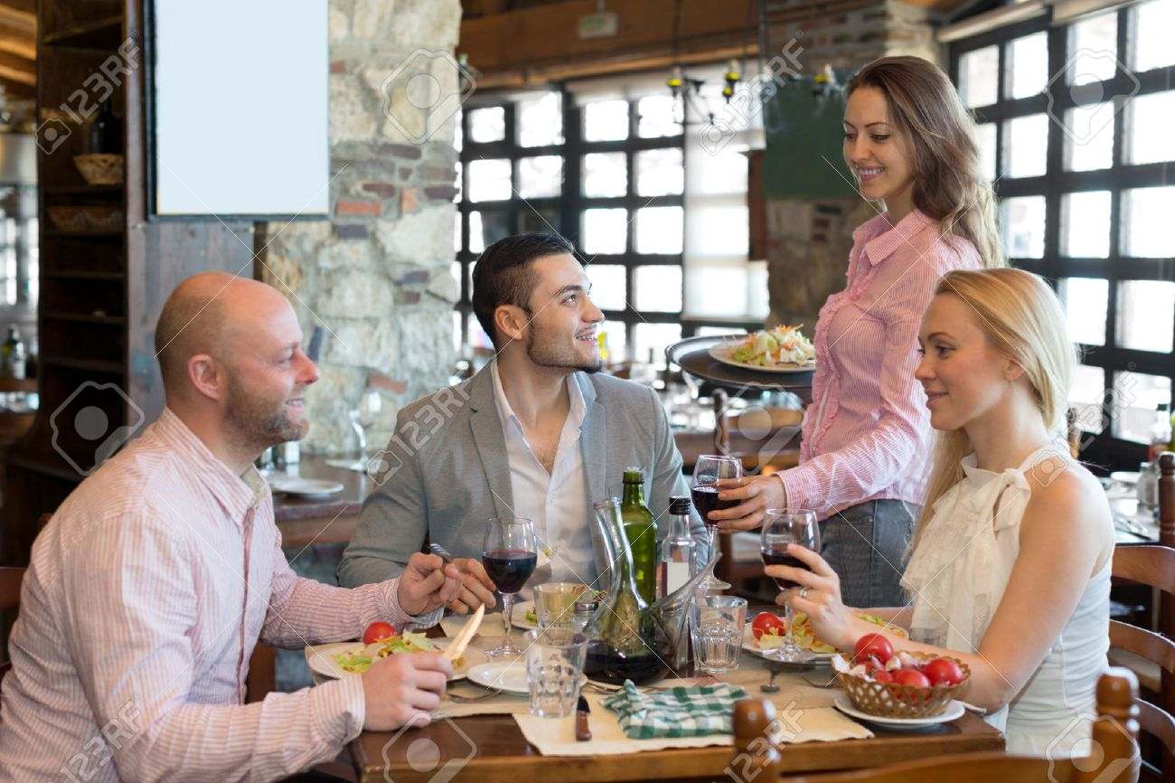 Happy group people having dinner at rural restaurant and drinking wine. Focus on the young man Stock Photo - 44971918