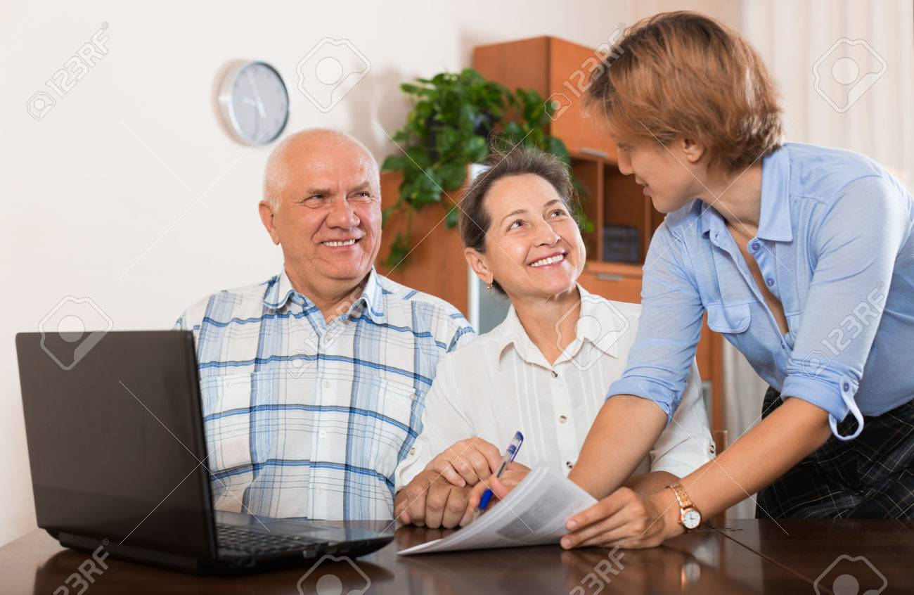 Mature couple answer questions of outreach worker with laptop in office Stock Photo - 45094840