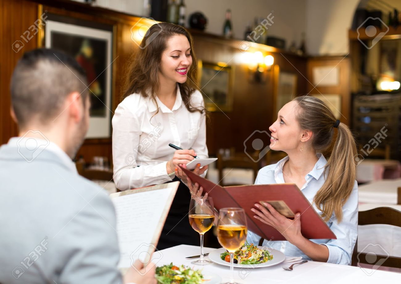 Hospitable waitress taking an order from a couple in a rural restaurant Stock Photo - 45301973