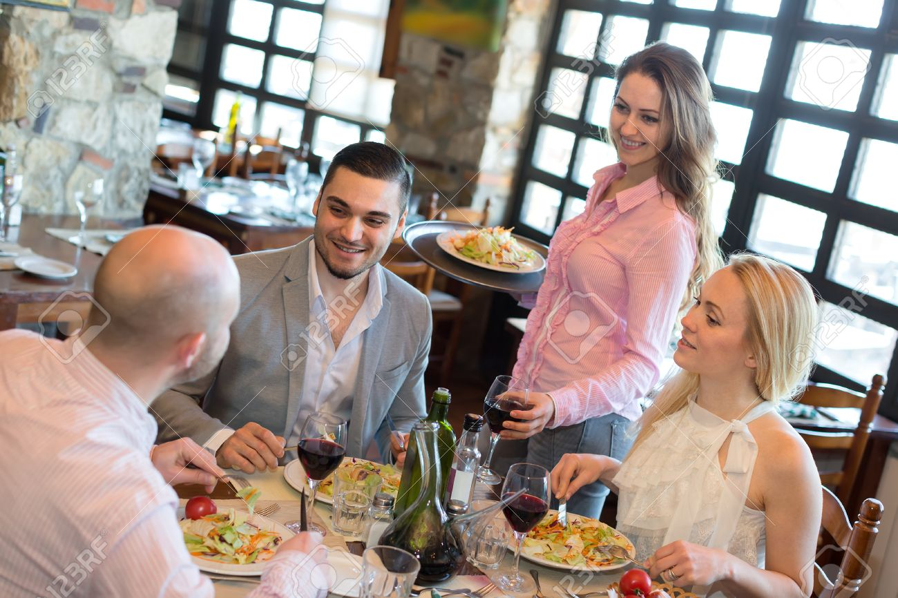 A company of people dining in a restaurant while smiling waitress is serving them Stock Photo - 45301076