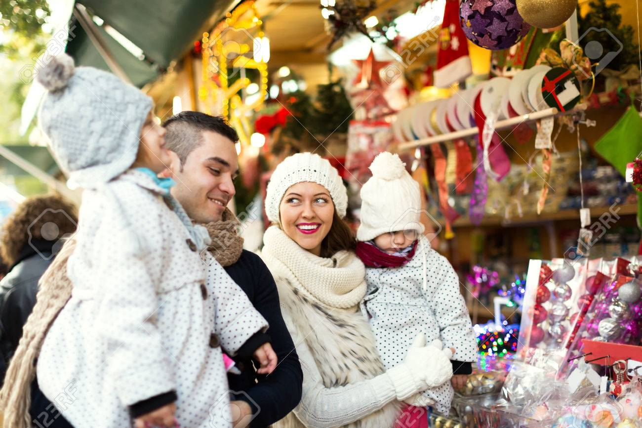 Happy family choosing Christmas decoration at Christmas market. Focus on woman and her daughter Stock Photo - 46515028