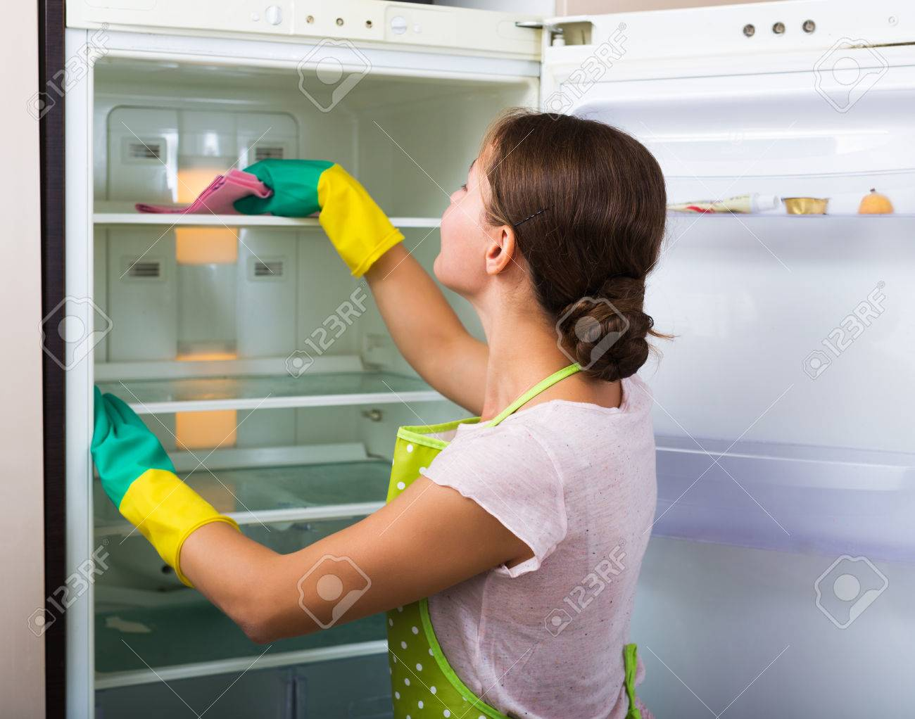 Adult housewife cleaning refrigerator inside and smiling Stock Photo - 46979493