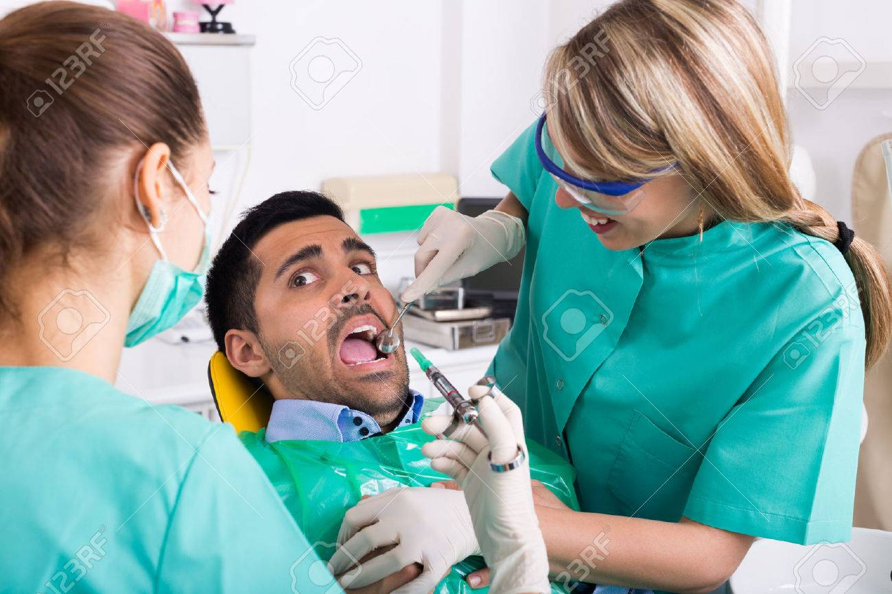 Dentist With Assistant And Scared Patient During Check Up At Dental Clinic Stock Photo