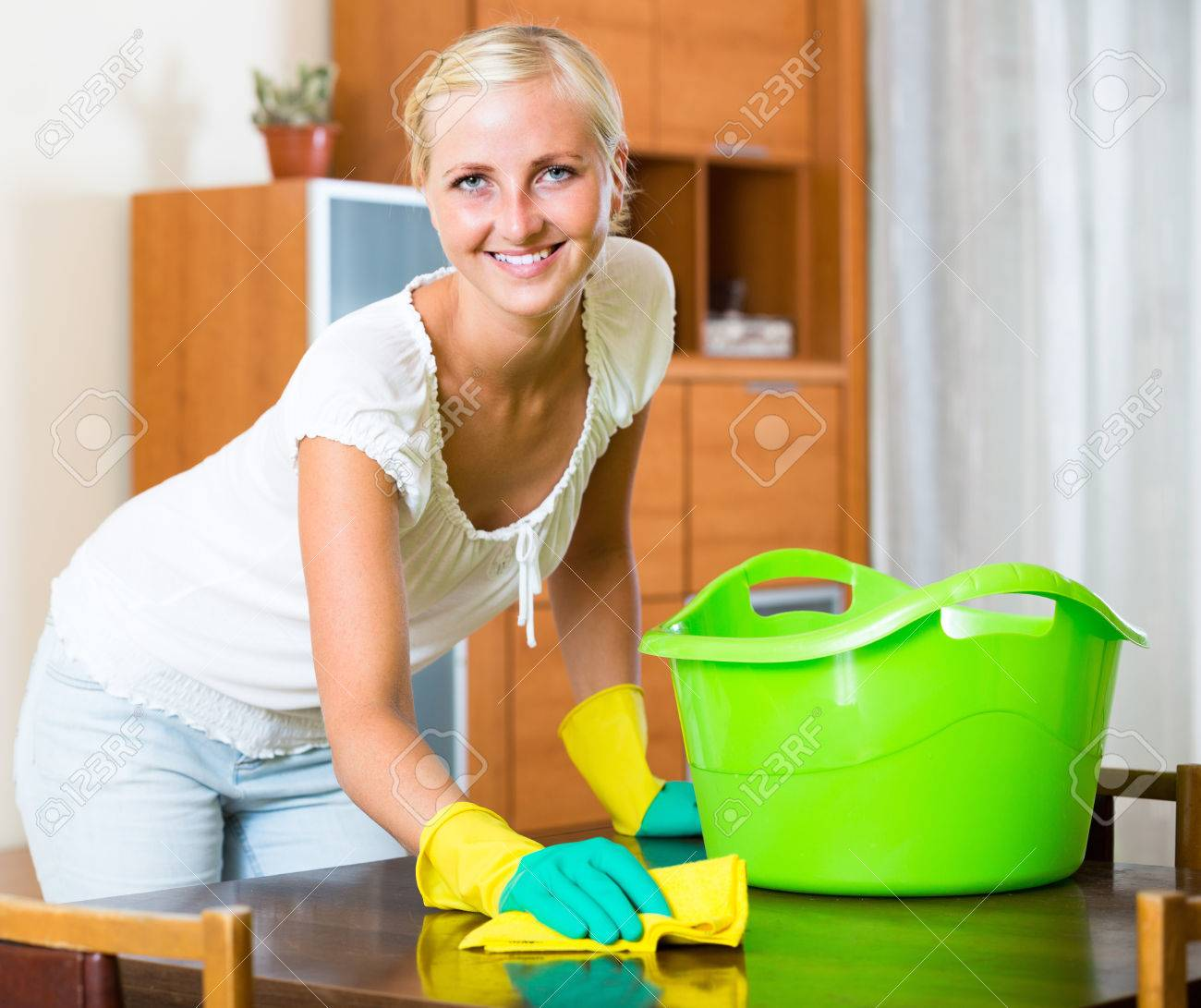 dusting furniture. Cheerful Girl In Rubber Gloves Dusting Furniture Living Room And Smiling Stock Photo - 47212933