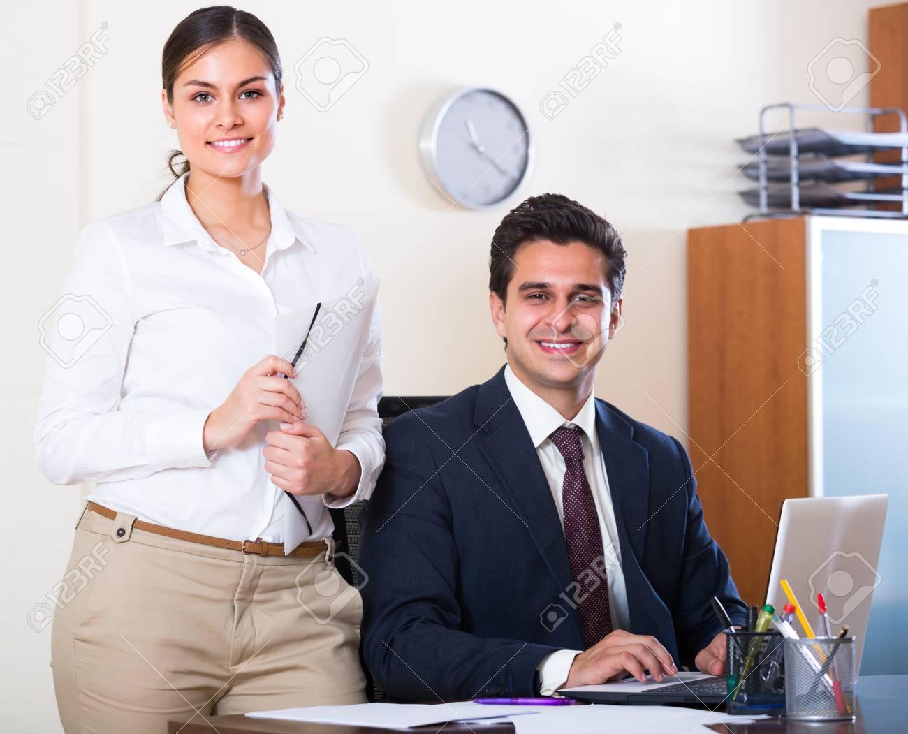 Heureux homme d affaires souriant et sa jeune secrétaire attrayant