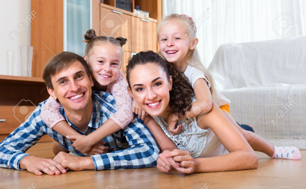 Family values: portrait of smiling parents with little girls indoors Stock Photo - 47626025