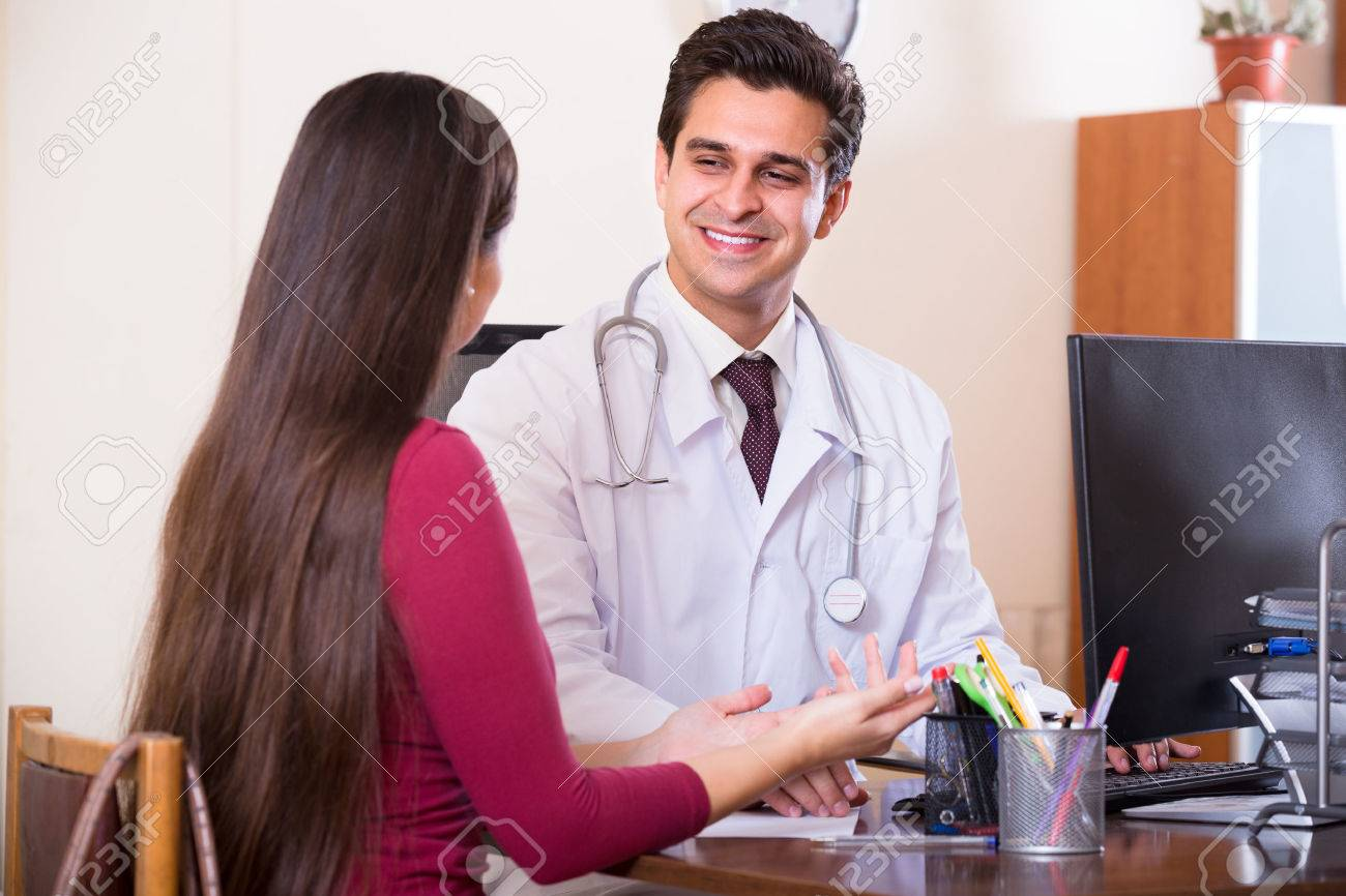 Positive doctor receiving ill patient at office and questioning Stock Photo - 48347931