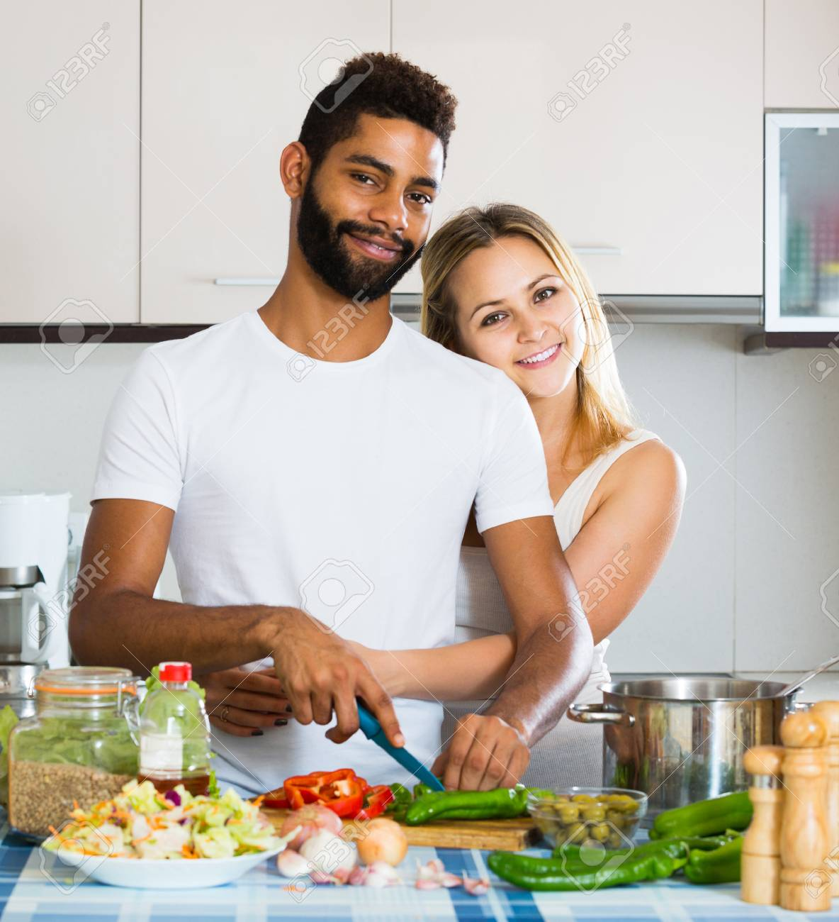 Happy Afro Man And White Smiling European Woman Cooking At Kitchen ...