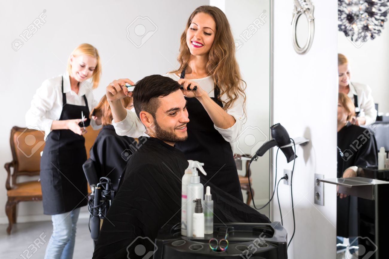 Beautiful young hairdresser working in a salon is making a haircut for a handsome man Stock Photo - 48544961