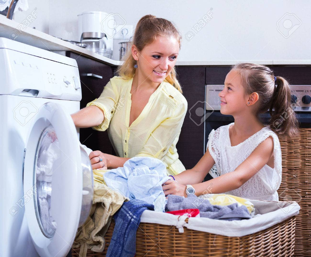 Young housewife and little girl doing laundry together - 51353226