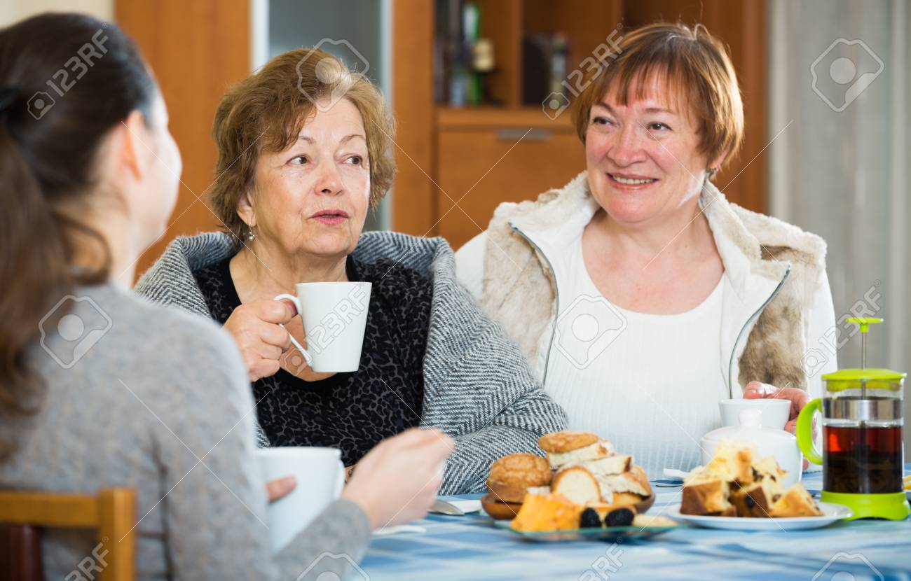 Mature women with adult girl drinking tea and chatting indoors Stock Photo  - 51531863