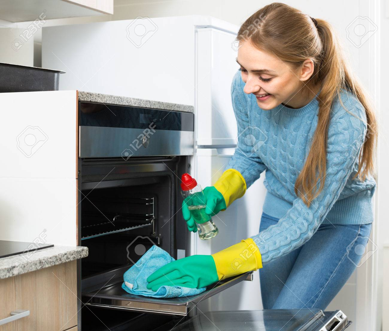 Young Maid Doing Oven Clean-up In Domestic Kitchen Stock Photo ...
