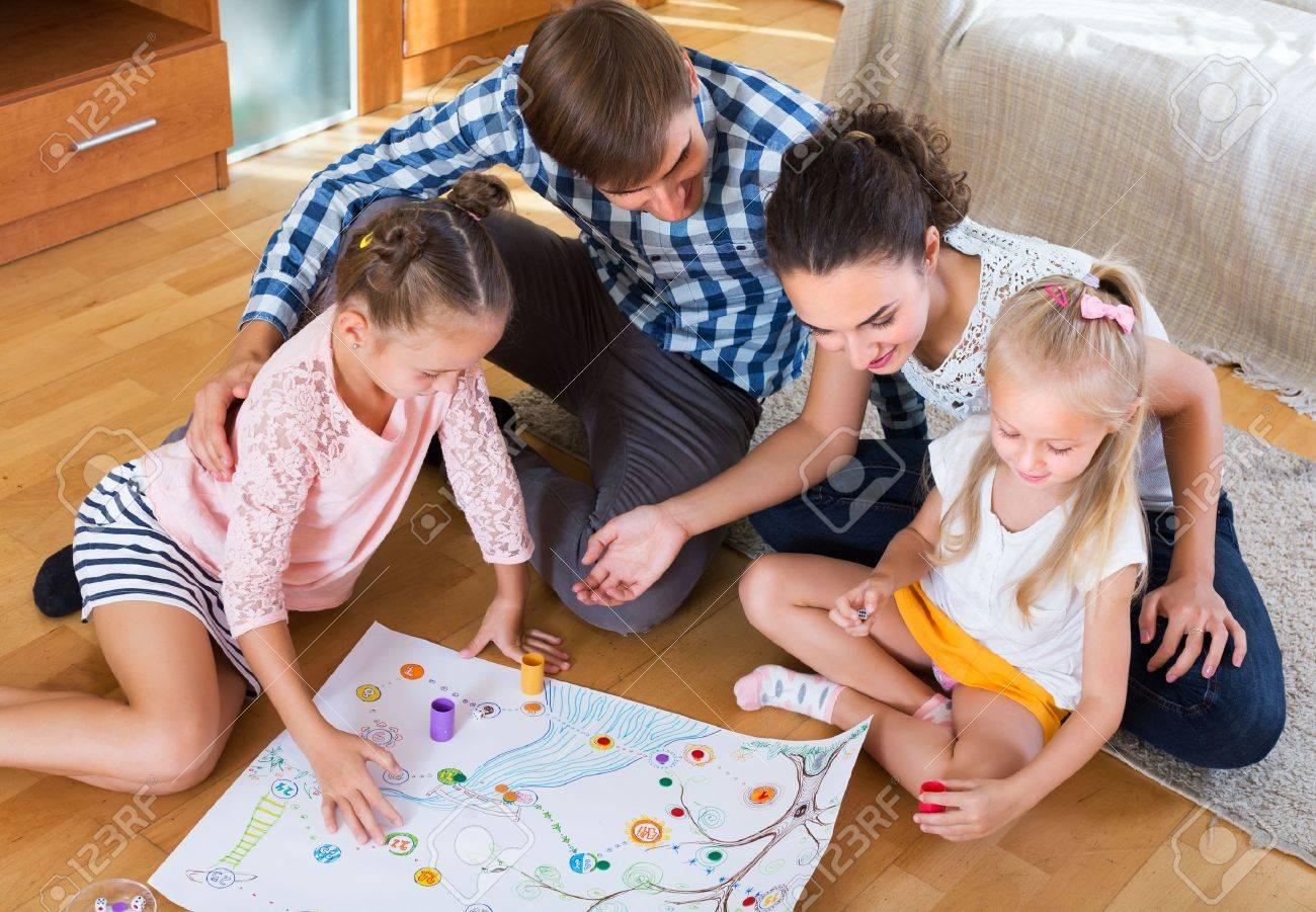 Familia Joven Feliz Con Dos Ninos Jugando Al Juego De Mesa En El