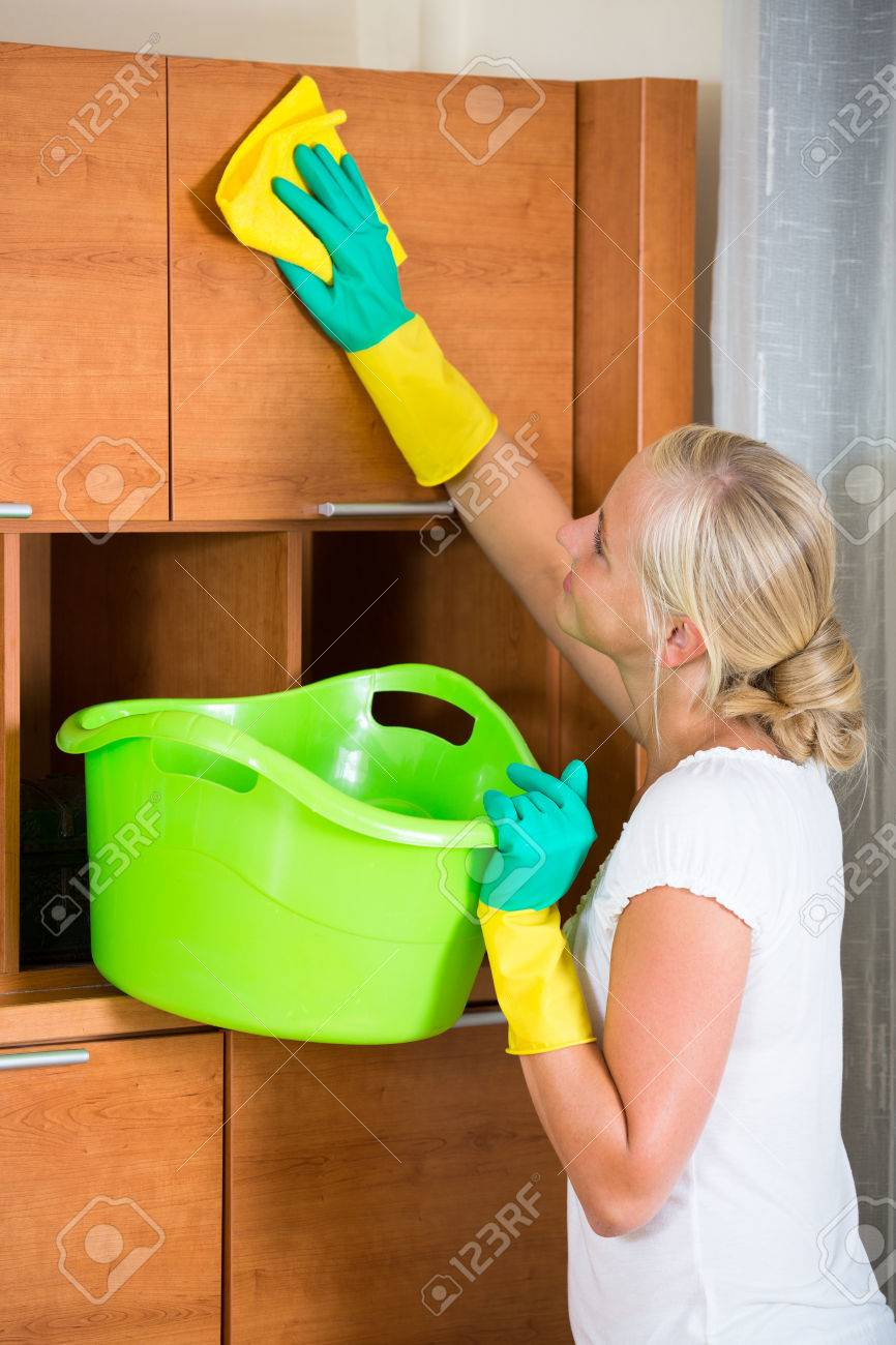 dusting furniture. Stock Photo - Young Woman In Rubber Gloves Dusting Furniture At Home And Smiling