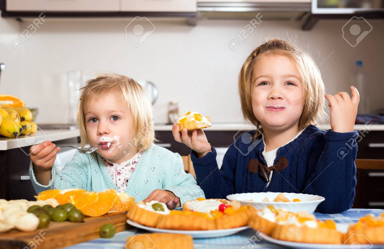 Two Junior Girls Eating Tasty Pastry Cream And Fruits Dessert Stock Photo Picture And Royalty Free Image Image 53775482