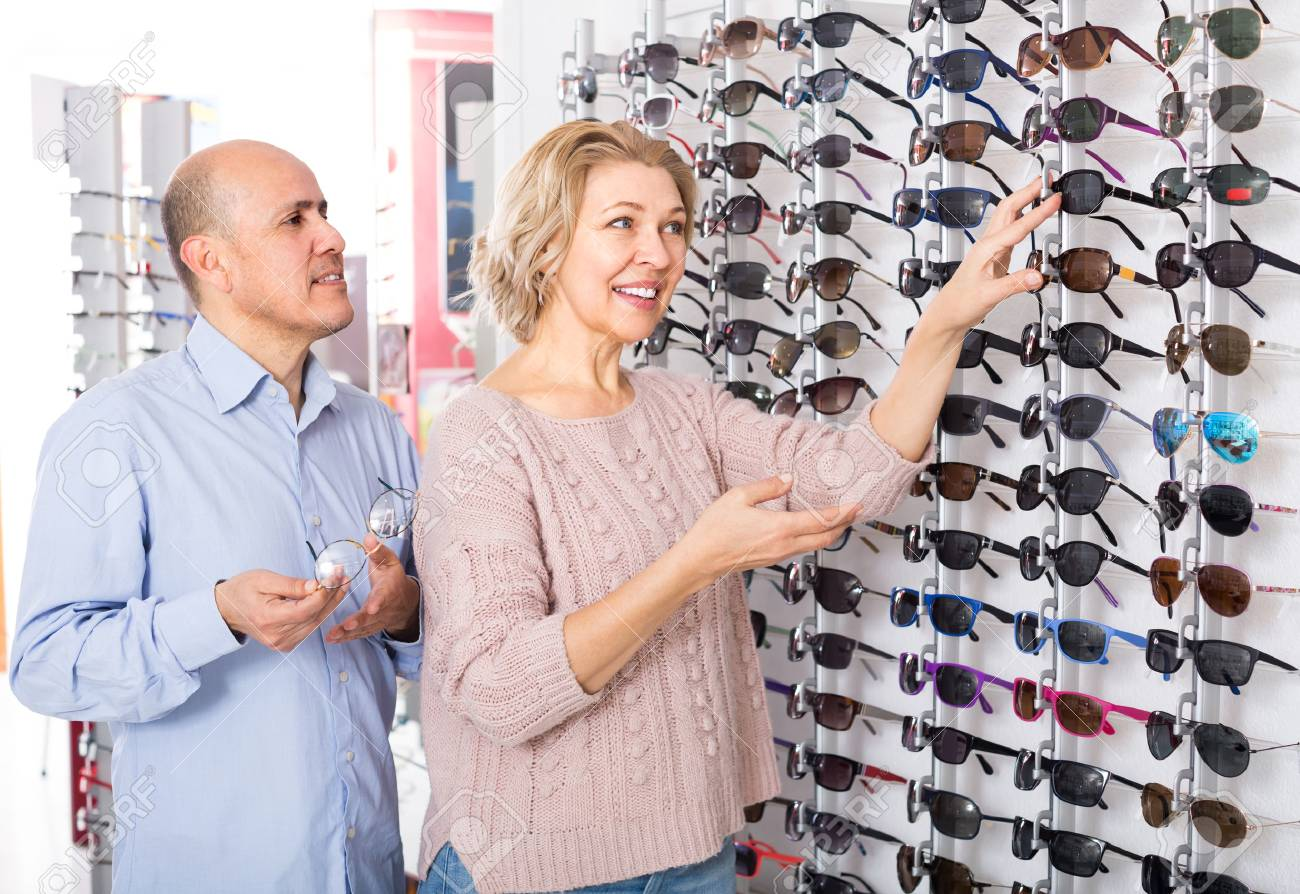 Smiling Pensioners Couple Choosing Frames For Sunglasses In Optics ...