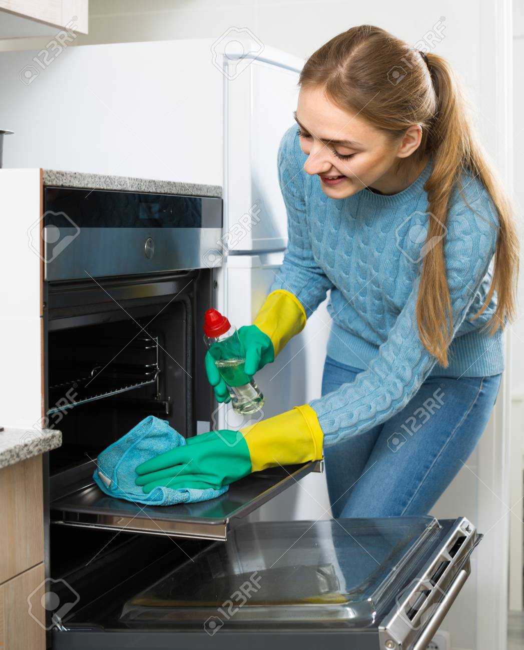 Positive Young Maid Doing Oven Clean-up In Domestic Kitchen And ...