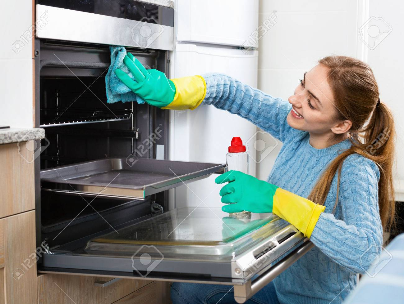 Cheerful positive adult girl in gloves removing snuff in oven - 55094843