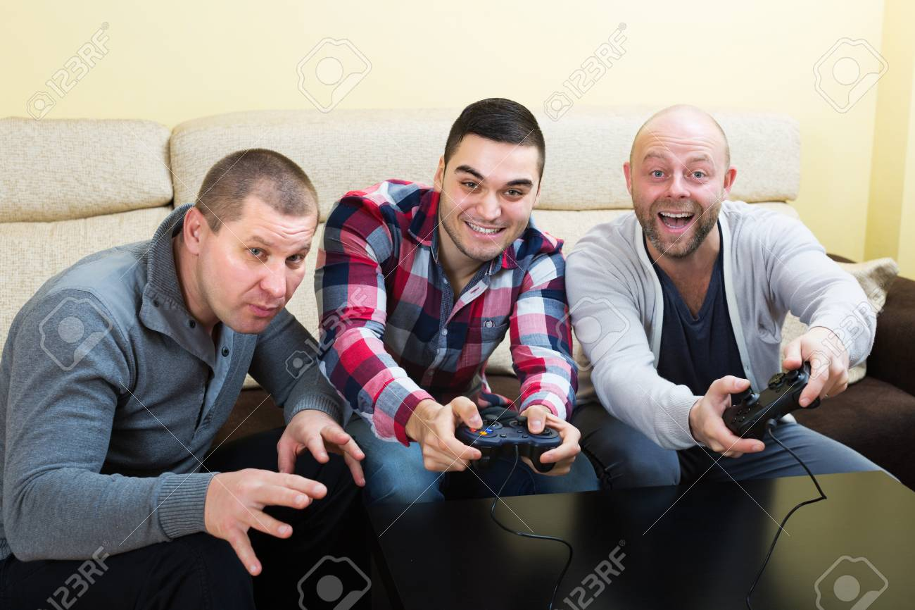 Adult friends relaxing with video game and laughing at home
