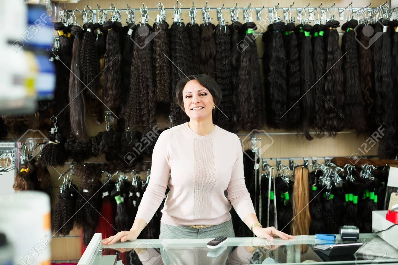 Friendly Saleswoman Offering Wide Assortment Of Wigs And Hair