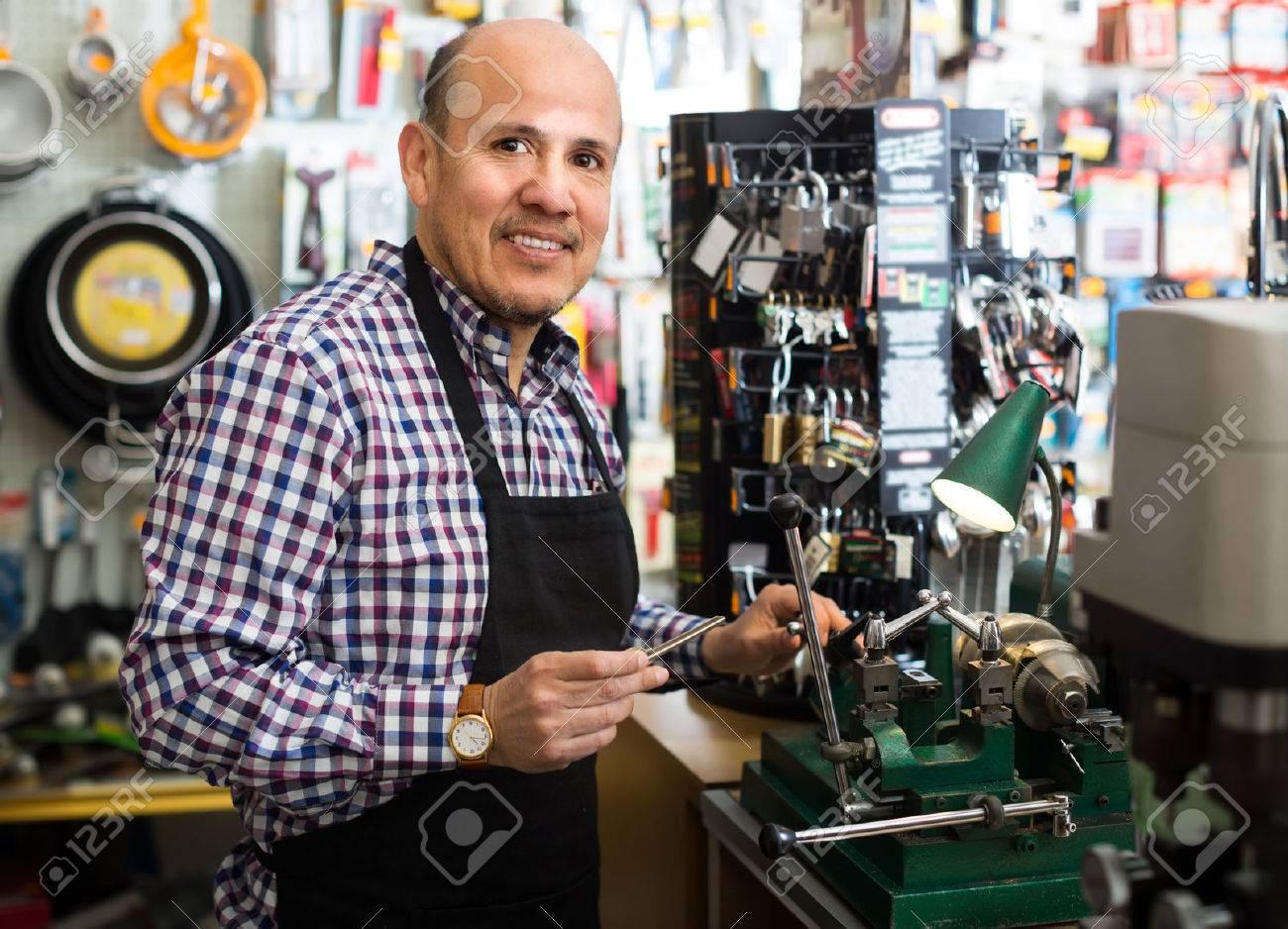 Elderly man in apron working in locksmith and making duplicates of keys Stock Photo - 56476374