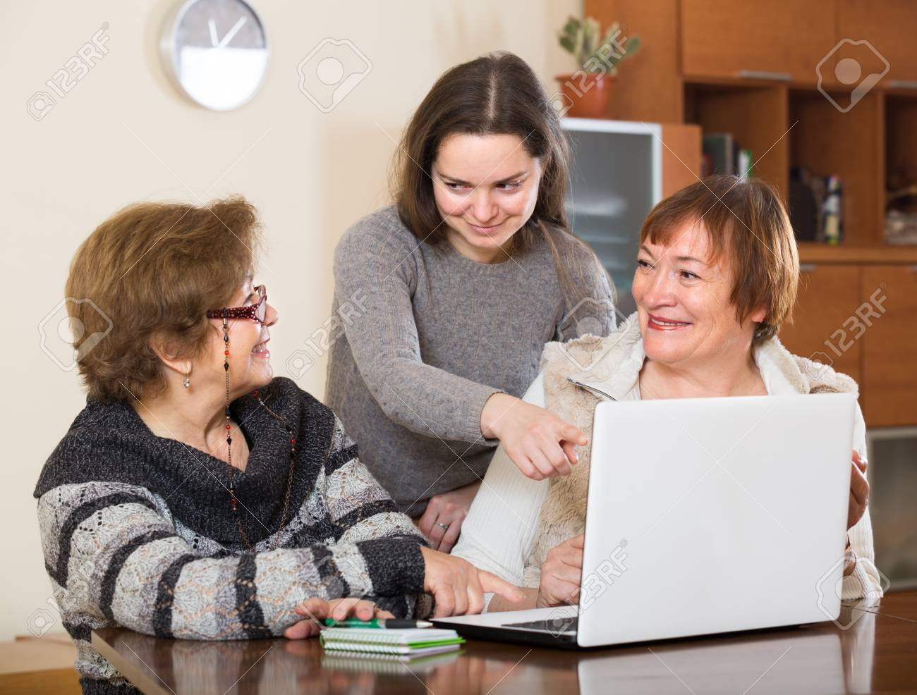 female pensioners and young relative making shopping list on laptop stock photo 58386234