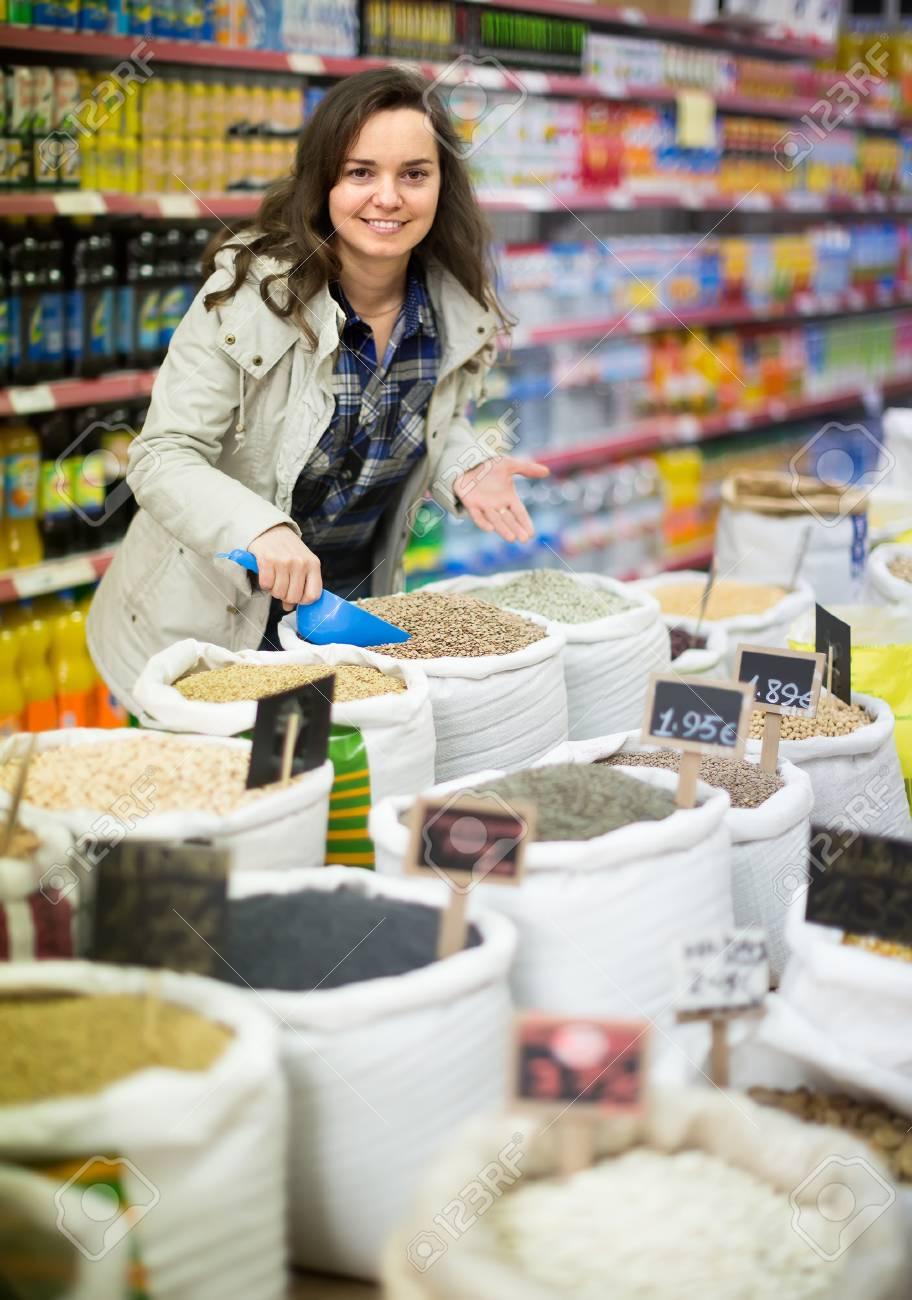 Joyful smiling young brunette woman buying groats in supermarket - 59146859