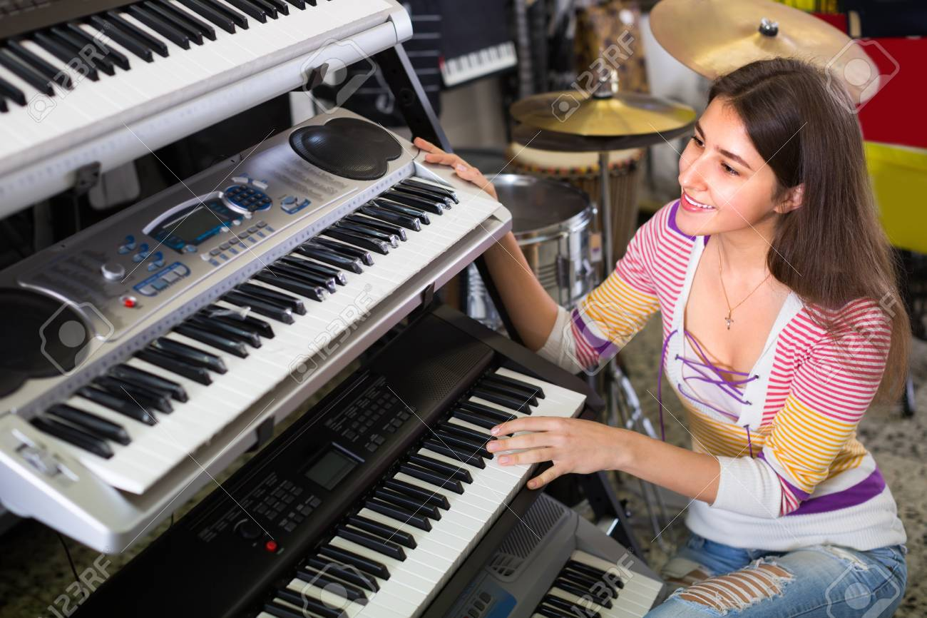 Joyful smiling longhaired girl choosing synthesizer in store