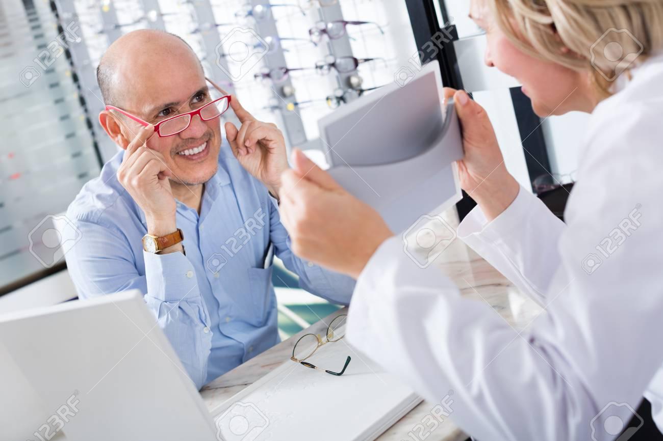 Senior Female Optician Offering A Glasses Frames To Elderly Client ...