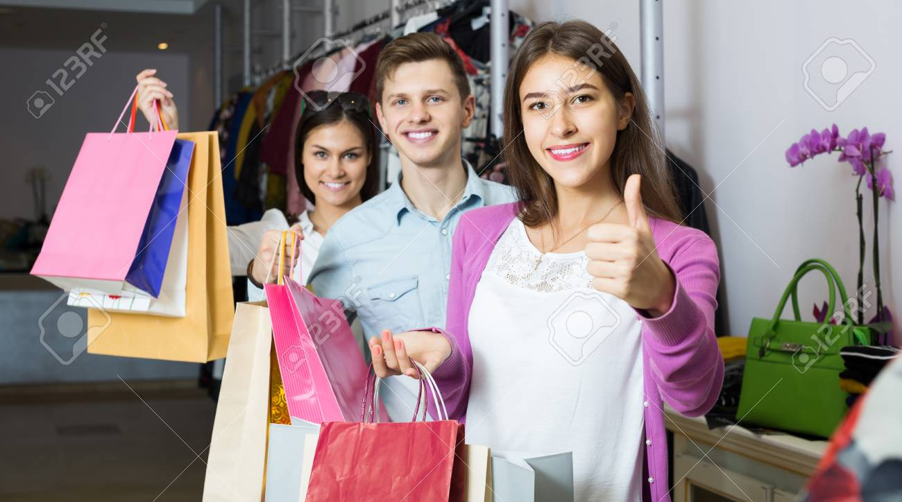 Stock Photo - Young spanish adults in good mood holding bags at clothing  store
