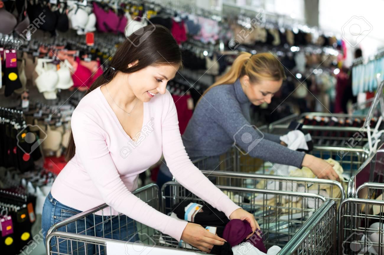 1d98db676f10 Dos mujeres jóvenes alegres mirando en cesta metálica con ropa interior en  la tienda