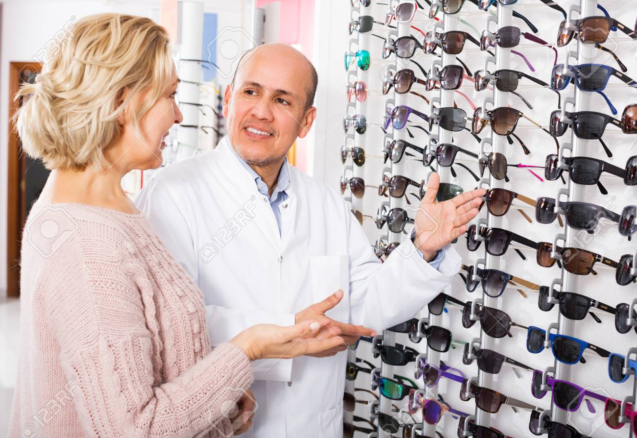 Senior Male Optician Offering Glasses Frames To Elderly Female Stock ...