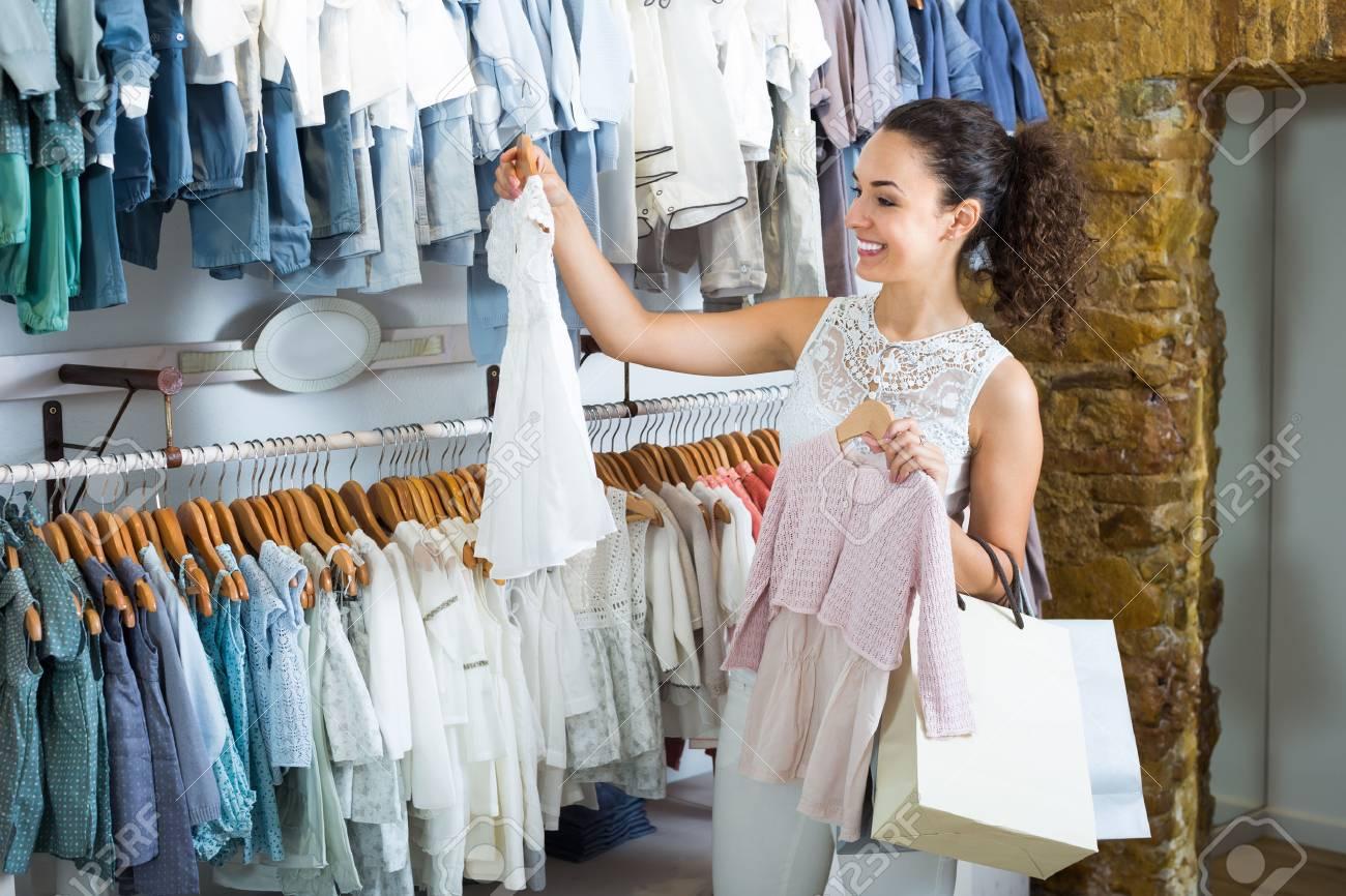 Mujer Alegre Joven Que Elige El Vestido Del Bebé En Boutique De Ropa De Niños