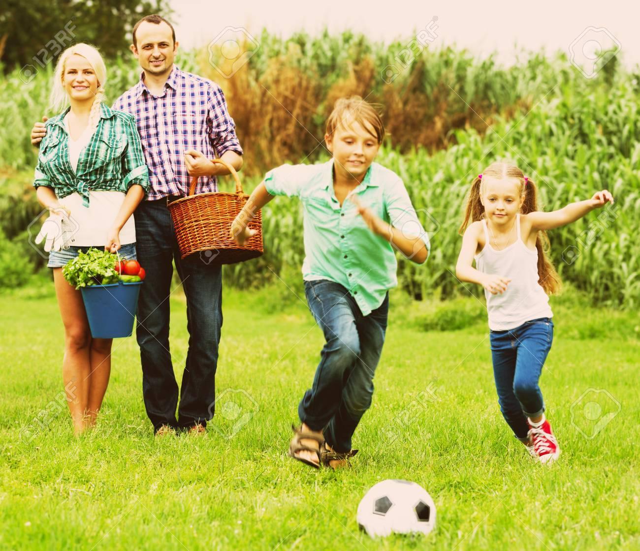 0525dab74c Archivio Fotografico - Attività estiva - coppia sposata con bambini che  giocano palla in casa di campagna. Concentrarsi sulla coppia