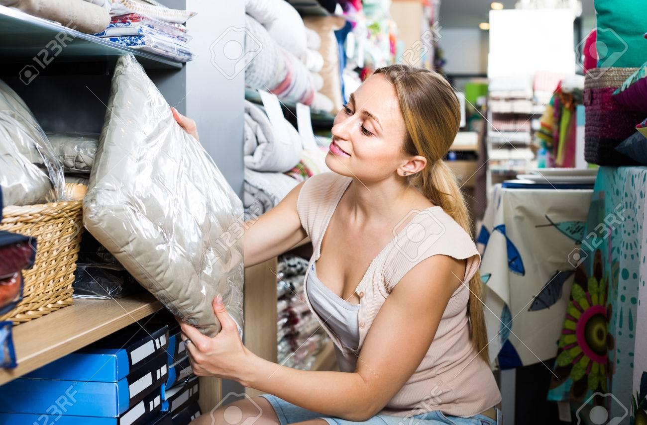 Foto de archivo - Retrato de almohada americano elección del cliente  femenina positivo en la sección de ropa de cama en la tienda 91f715fe480e