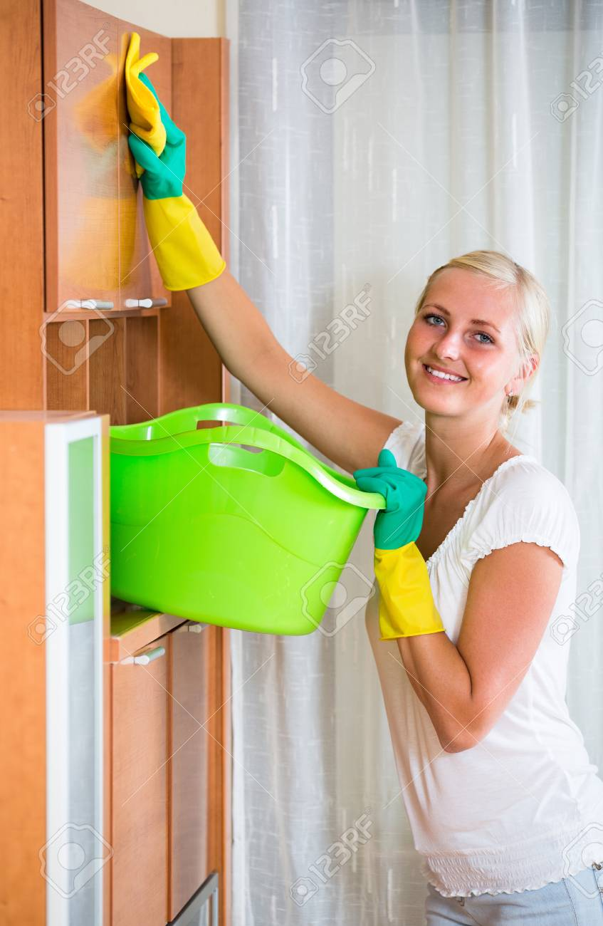 dusting furniture. Cheerful Blonde Girl In Rubber Gloves Dusting Furniture At Home And Smiling Stock Photo - 62892551 W