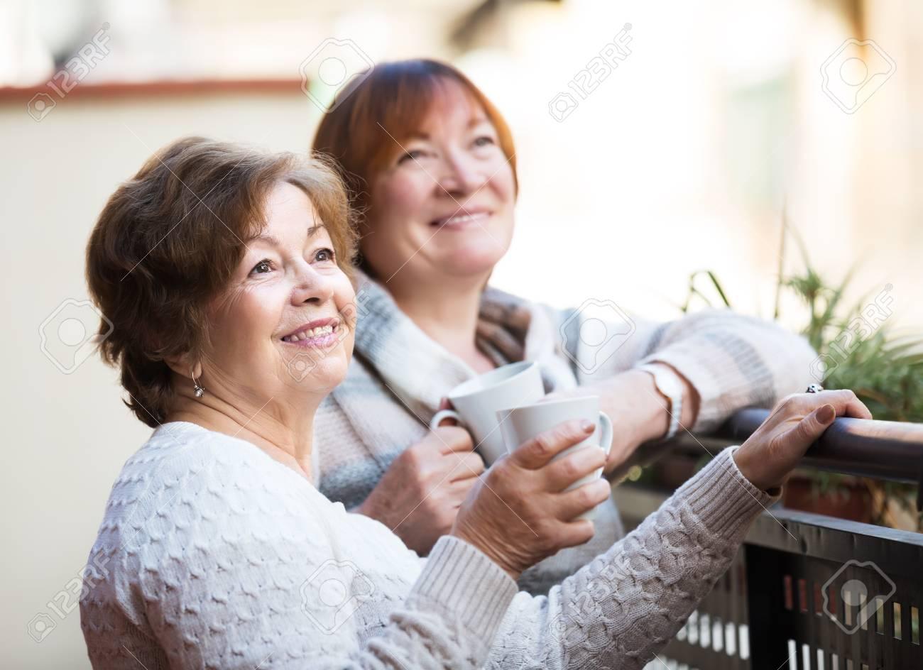 Amigas Maduras dos amigas maduras bebiendo café en el patio y sonriendo