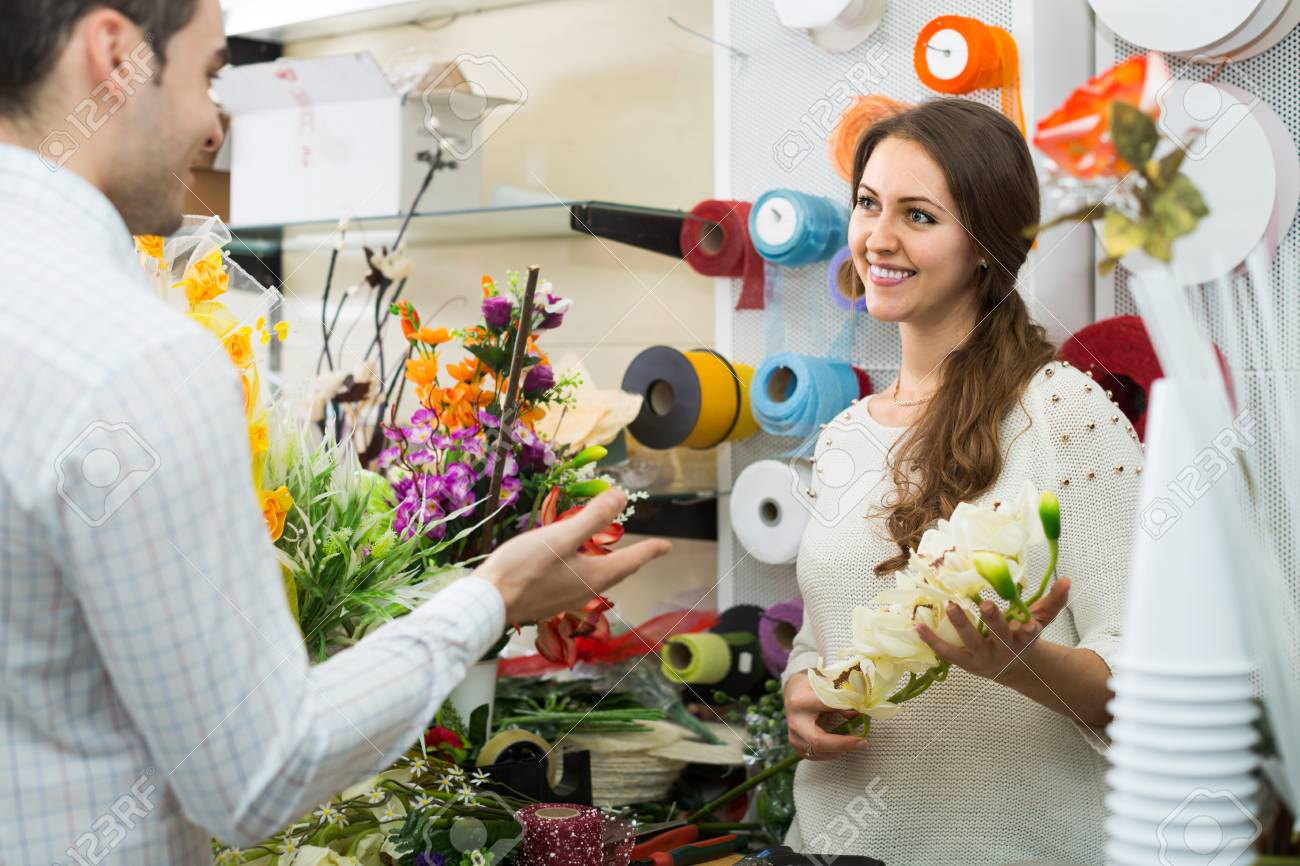 Woman seller helping to pick floral bouquet of flowers man at stock photo woman seller helping to pick floral bouquet of flowers man at flower shop izmirmasajfo