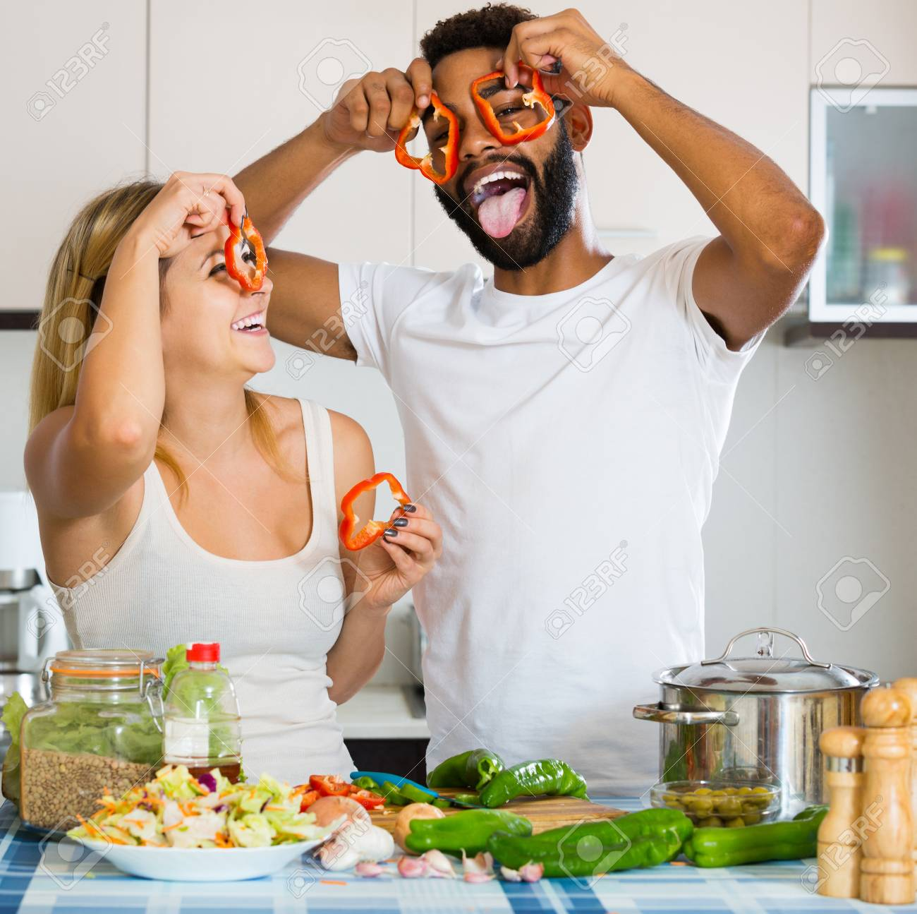 Happy Afro Man And White Positive American Woman Cooking At Kitchen ...